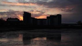Tid schackningsperiod av solnedgången bak ett modernt flerbostadshus arkivfilmer