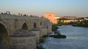 Tid schackningsperiod av turister som korsar den berömda romerska bron av Cordoba, Spanien över den Guadalquivir floden lager videofilmer