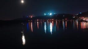 Tid schackningsperiod Månelöneförhöjningarna ovanför nattstaden Ett fartyg seglar på floden arkivfilmer