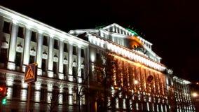 Tid schackningsperiod Sikt av byggnaden beautifully exponerad av ljusen av stadsbanken på natten, då bilar är inflyttningen cent arkivfilmer