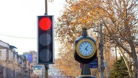Tid schackningsperiod: trafikljus med en klocka på stadsbakgrunden med träd lager videofilmer