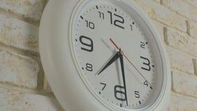Tid sju timmar trettio minuter Timelapse Rund vit klocka som hänger på tegelstenväggen lager videofilmer