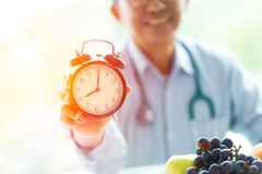Tid som bantar doktorn med den sunda klocka- och fruktgodan Arkivbilder