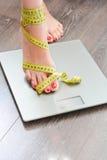 Tid som förlorar kg med kvinnafot som kliver på en viktskala Fotografering för Bildbyråer