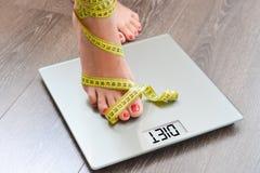 Tid som förlorar kg med kvinnafot som kliver på en viktskala Royaltyfri Bild