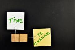 Tid som ska ändras, två pappers- anmärkningar på svart bakgrund för presenta Fotografering för Bildbyråer