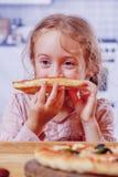 Tid som ska ätas! Gullig liten blond flicka med pizza Lyckligt barn som har den roliga äta matställen royaltyfri fotografi