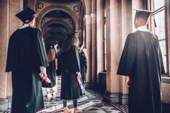 Tid som ska klivas in i en ny värld Skott för bakre sikt av en grupp av studenter som står i universitetkorridoren royaltyfria bilder