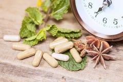 Tid som äter organisk örtkapselmedicin Arkivbild