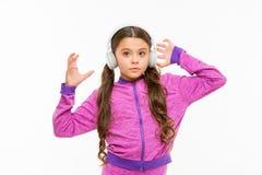 Tid som vilar den aktiva flickan för att tycka om musik som spelar i hörlurar Idrotts- koppla av f?r liten flicka som isoleras p? royaltyfri bild