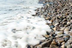 Tidal bore. Surf, colored pebbles, sea foam Stock Photography
