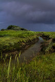 Tidal creek with stormy sky. In Lincolnshire Royalty Free Stock Image