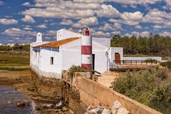 Tidal Mill at low tide, Algarve, Portugal. The restored Tidal Mill at low tide on the Ria Formosa Nature Park near Olhao on the Algarve, Portugal. The tidal stock images