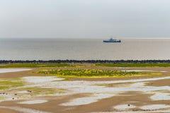 Tidal mud flat of the island Ameland. Boat sailing past tidal mud flat of the island Ameland, the Netherlands royalty free stock image