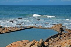 Tidal pool in the sea at Ramsgate, Kwazulu Natal. Waves rolling over rocks towards calm tidal pool at Ramsgate, Kwazulu Natal Royalty Free Stock Photography