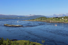 Tidal stream Saltstraumen near Bodø, Norway. Tidal stream with fishing ships, some wooden houses and mountains in the background on a very clear blue day Royalty Free Stock Images