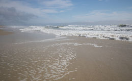 Tidal wash. Waves gently wash over larger areas of beach as the tide rolls in Stock Photos