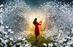 Tidal wave of book pages. A woman holding a book is surrounded by giant waves of pages Stock Image