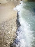Tidal wave  and rocky sand. Chasing the coastal tide in Curazao Stock Photography