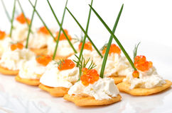 Tidbits with caviar. Salty crackers with cream cheese and red caviar Stock Photos
