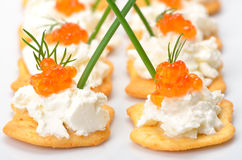 Tidbits with caviar. Salty crackers with cream cheese and red caviar Royalty Free Stock Photo