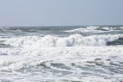 Tide. White foam on ocean surf at beach royalty free stock photo