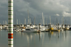 Tide gauge. A graduated pole for measuring high tides in a marina Royalty Free Stock Image