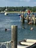 Dock jumping. When the tide is high, all ages of kids adults go to the dock and hang out and jump off and sing and dance Stock Photo