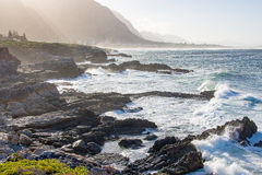 Tide meets rocky shore at Hermanus. Tidal movement and waves on a calm day at Hermanus, South Africa, with hazy mountains in the background Stock Photos