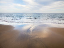 Tide is out. Wide stretch on wet sand with reflections, left by the tide going out Stock Photography