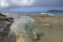 Tide pool on rocky Caribbean shore with rain at sea Stock Image