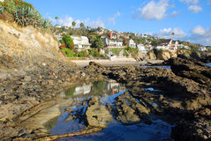 Tide pool and rocky shoreline near Woods Cove, Laguna Beach California. A rocky shoreline and tide pool borders picturesque Woods Cove (upper center) south of Stock Image