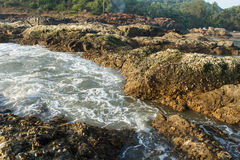 Tide at the rocks. Blue sea, tide, wave, white foam, living water, reefs, rocky cliff, old ragged rocks, marine sediments, dangerous bay, element, water power royalty free stock photo