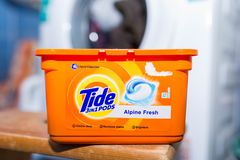Tide washing liquid capsules in front of a washing machine. stock photo