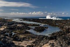 Tidepool op Hawaiiaans vulkanisch strand Zwarte rotsen in voorgrond; overzees, blauwe hemel en wolken op achtergrond stock foto's