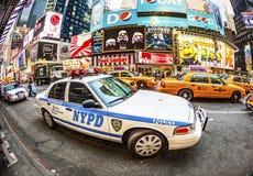 Tider kvadrerar i New York i eftermiddagljus med polisbilen Arkivbild