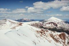 tidig liggandebergfjäder snöig berg Arkivbild