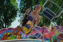 Tidig mässa i Ouchy Lausanne Modern med barn har mycket gyckel i de karusell Arkivfoto