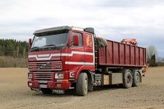 Tidig röd Volvo FH12 lastbil som parkeras på ett fält Arkivfoto