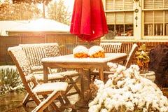 Tidig snö - utomhus- tabell och stolar med två stålarnolla-lyktor och ett solparaply på en uteplats under en snödusch med huset royaltyfri fotografi