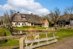 Tidig vårsikt på Giethoorn, Nederländerna, en traditionell holländsk by med kanaler och lantlig lantgård för halmtäckt tak arkivfoton