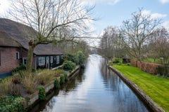 Tidig vårsikt på Giethoorn, Nederländerna, en traditionell holländsk by med kanaler och lantliga lantgårdhus för halmtäckt tak arkivbild