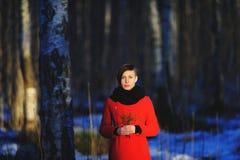 Tidig vårstående av den gulliga attraktiva allvarliga unga flickan med värmehalsduken för mörkt hår och det röda omslaget som ser Royaltyfri Fotografi