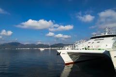Tidigt på morgonen på hamnstaden Illuminaten för resningsol ett stort vitt färjakatamarananseende på pir royaltyfria foton