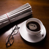 Tidning, exponeringsglas och kopp på skrivbordet Arkivbilder