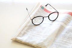Tidning med glasögon på brun bakgrund Royaltyfria Foton