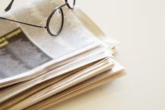 Tidning med glasögon på brun bakgrund Fotografering för Bildbyråer