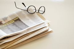 Tidning med glasögon på brun bakgrund Royaltyfri Foto
