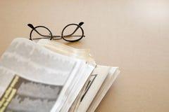 Tidning med glasögon på brun bakgrund Arkivfoto