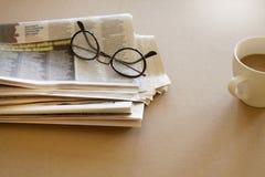 Tidning med glasögon på brun bakgrund Royaltyfri Fotografi